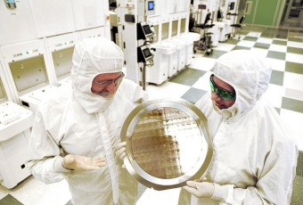 Dr. Michael Liehr (left) of SUNY Polytechnic Institute's Colleges of Nanoscale Science and Engineering and Bala Haran (right) of IBM Research inspect a wafer comprised of 7nm (nanometer) node test chips in a clean room in Albany, NY. IBM Research